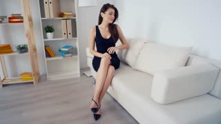Elegant calm woman in black dress and shoes with long brunette hair sitting on sofa in interior in minimalism style