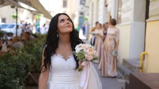 Elegant emotional brunette bride in stylish white dress with a rose bouquet walking in old street