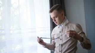 Elegant young fashion groom in beige shirt dressing bow-tie standing near window