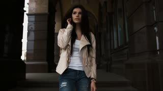 Fashion style portrait of young beautiful calm female model posing at city street with magnificent old architecture