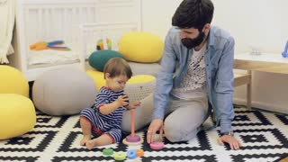 Father and child boy playing construction game together at home on the floor.