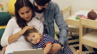 Fatherand mother with little boy using digital tablet at home