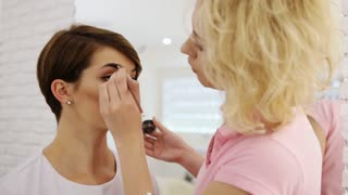 Female beauty. Makeup artist stylist applying with brush cosmetic on eyebrow of young brunette woman