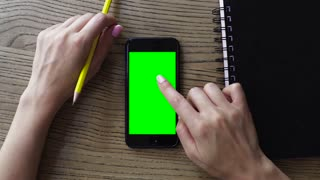Female hand using smart mobile phone with a green screen on wooden table, overhead view