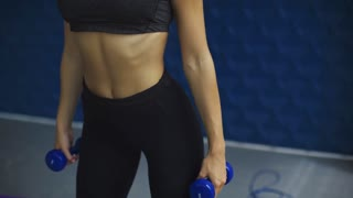 Fitness, sport, training and lifestyle concept - close-up of woman with dumbbells exercising and doing squats