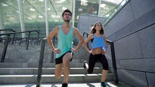 Fitness woman and man doing jump squats for leg explosive strength workout. Friends or lovers training together.