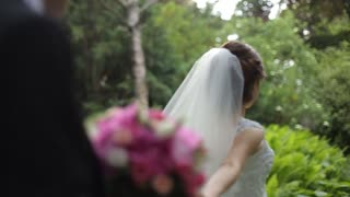 Follow me. Beautiful young bride in white veil holds the hand of groom with bouquet in outdoors.