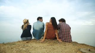 Four friends sitting on the beach.