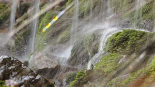 Fresh water stream with waterfall in mountain forest, close up