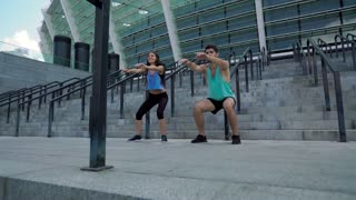 Full-length of couple doing side squat attacks on stairs at modern stadium