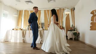 Full-length of young amazing bride and groom dance their wedding dance in modern interior of restaurant