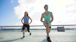 Full length of young couple exercising, personal trainer man coach and woman exercising squats at bridge