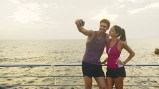 Funny couple taking pictures after long distance that they have run together.