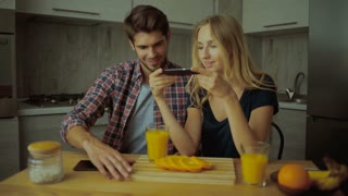 Funny couple taking pictures of tasty oranges in the kitchen.