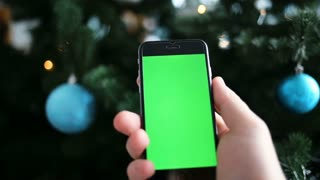 Green screen display phone at New Year night celebration in front of Christmas tree