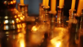 Group of dimly lit, burning white candles create mood, ambiance, close up, black background