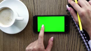 Hand holding smart phone with coffee on wood desk. Green screen and can be add your texts