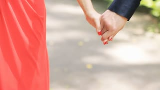 Handhold of a couple walking in the park in slow motion