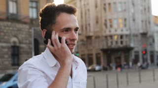 Handsome and positive guy actively talking on cellphone outdoors during sunset in the middle of european city.