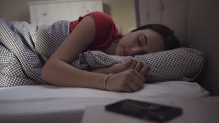 Handsome brunette girl is  wakes up in a bed and starts to use her mobile device.