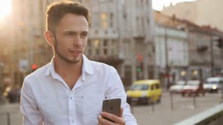Handsome caucasian male in his 20s doing selfie outdoors in middle of european city center. Guy using frontal camera on his smartphone