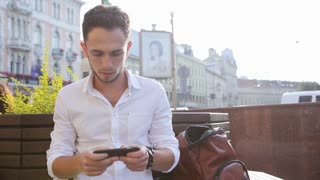 Handsome caucasian man sitting in a square and using his mobile phone for texting. Male in his 20s creating an sms on smartphone. Close-up male hands using phone for making an sms