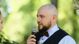 Handsome elegant bald groom taking vows at the outdoors wedding ceremony