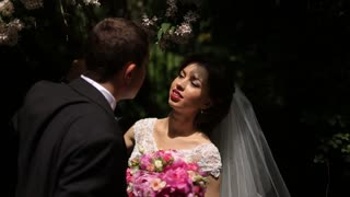 Handsome groom kissing the bride with bouquet on a background of dark green leaves, couple touching noses of each other