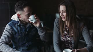 Handsome male and female in their 20s sitting at the cafe, drinking tea and coffee, have a nice talk and smiling.
