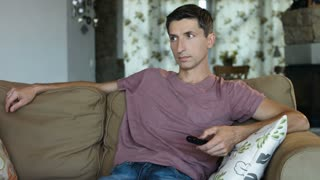 Handsome man changing TV channels with remote control sitting on sofa at home