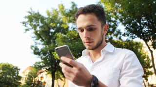 Handsome stylish male in his 20s texting outdoors by using smartphone.