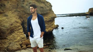 Handsome young smiling man in stylish clothes, posing on the windy beach.