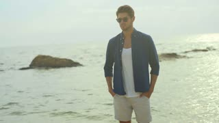 Handsome young smiling man, wearing expensive casual clothes , posing on camera on the beach.
