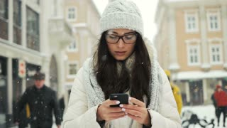 happiness, winter holidays, christmas, beverages and people concept - Beautifulwoman wearing winter coat and smiling happy while sending message with cellphone in the city