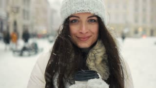 happiness, winter holidays, christmas, beverages and people concept - Cheerful gorgeous brunette in winter fashion holding disposable cup on urban background