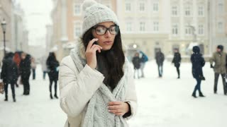 happiness, winter holidays, christmas, beverages and people concept - happy girl talking on the phone city snow winter christmas