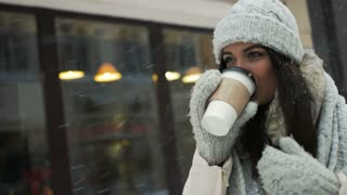 happiness, winter holidays, christmas, beverages and people concept - Pretty young brunette drinking coffee outside on winter