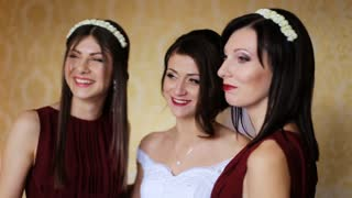 Happy beautiful bride and bridesmaids wearing same cherry dresses posing on camera and smile.