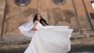 Happy beautiful emotional sexy brunette bride dancing with her dress and white veil, while happy groom standing on background