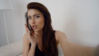 Happy brunette girl dressed in black lip rounding sending kisses making self portrait - point of view of camera.