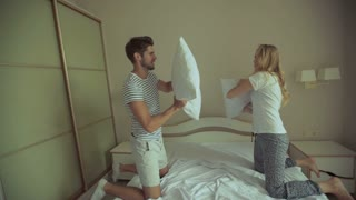 Happy Couple Having Pillow Fight in Hotel Room. They Wear Underwear and stand on bendend Knees on the Bed. Everyone is Holding a Pillow. The Woman has Long Blonde Hair, the Man has Black Short Hair.