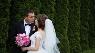 Happy gorgeous bride with bridal pink bouquet and stylish groom hugging with gentle, kissing on background of sunny trees forest