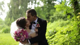 Happy groom is kissing his beautiful bride wearing gorgeous wedding dress and veil in her cheek at raining day