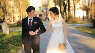 Happy joy caucasian groom and bride happily go on the roadshot in slow motion  close up