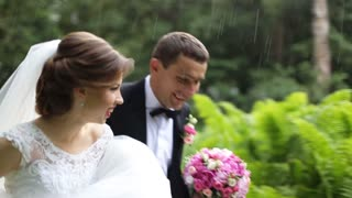 Happy married couple running under a downpour rain and laughing