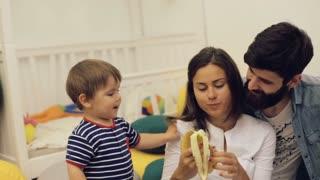Happy parents feeding toddler boy healthy food at home, cute baby eating banana indoors
