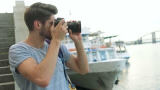 Happy photographer using his photo camera.