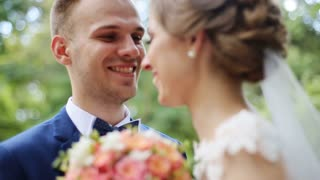 Happy smiling bride and groom on their wedding day posing with bridal bouquet outdoors