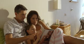 Happy smiling caucasian family laying in bed, mother, father and daughter reading magazine