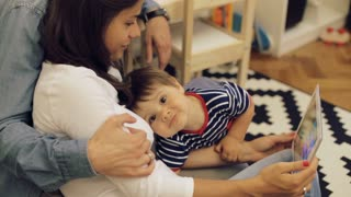Happy smiling mother and adorable baby boy with tablet pc